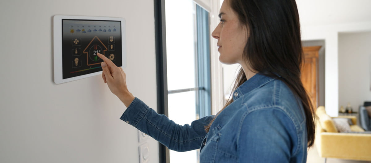 woman adjusting a thermostat