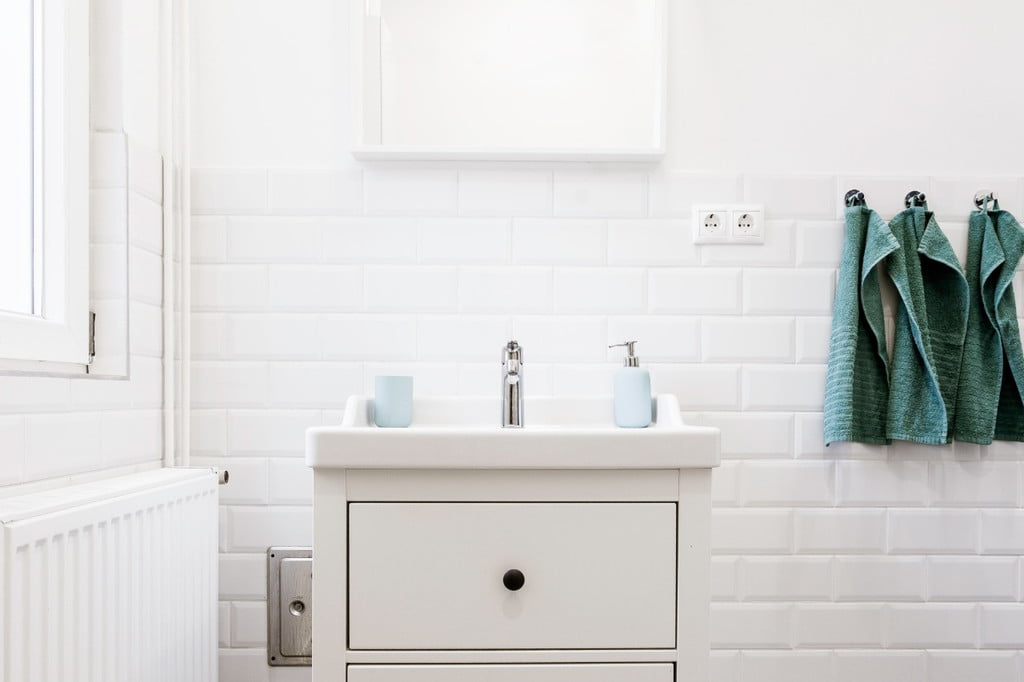 White bathroom sink with hanging towels