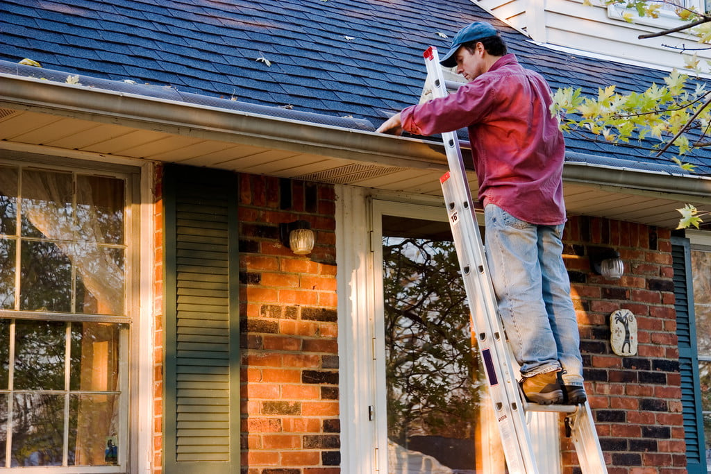 man on a ladder cleaning rain gutters
