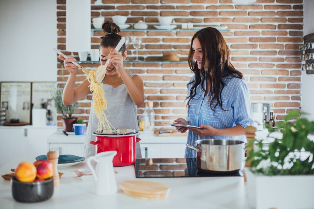two women cooking together in kitchen