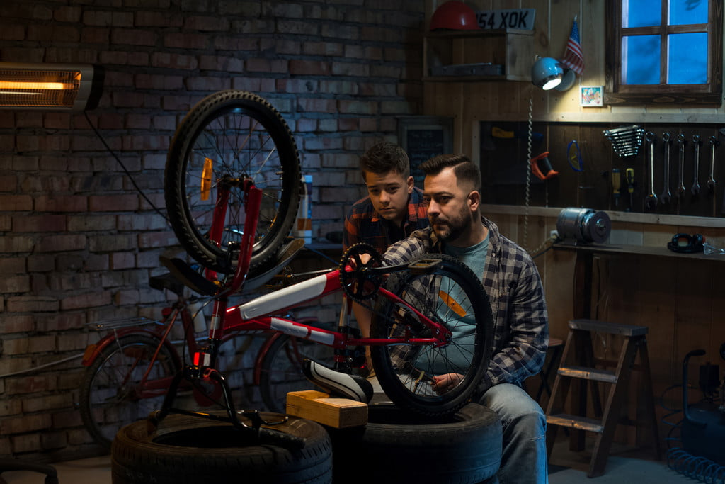 Dad and son working on a bike in the garage