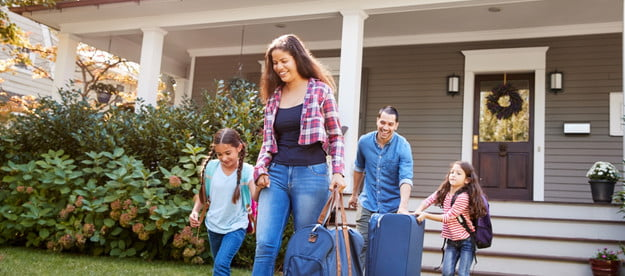 family carrying luggage and leaving home