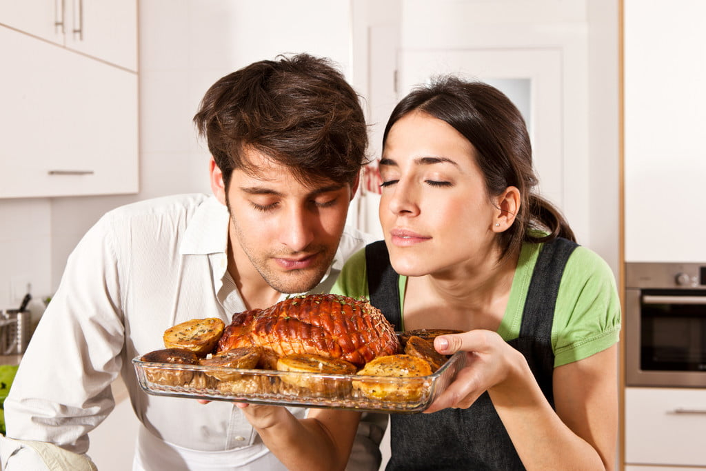 couple holding cooked turkey