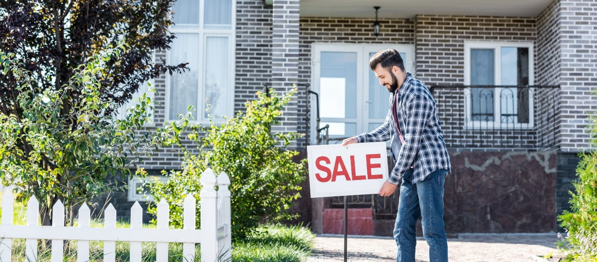 man in front of house for sale