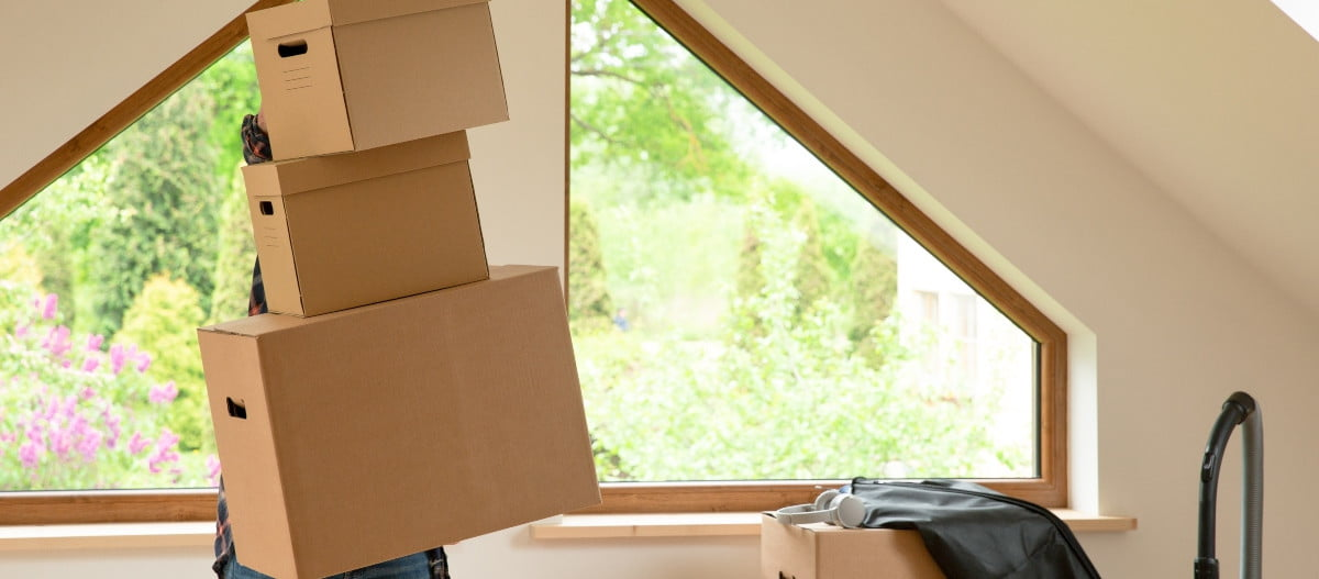 person organizing boxes in their finished attic
