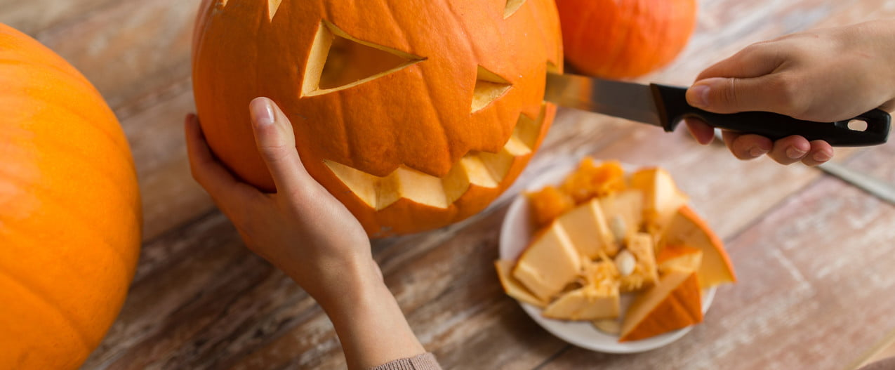 person with knife cutting a pumpkin for halloween