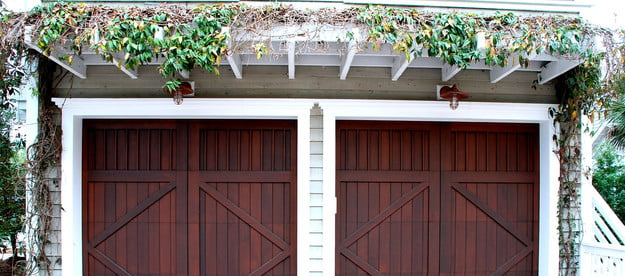 Cherry-colored double garage doors with ivy above