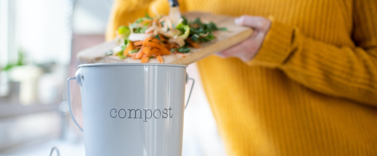 Woman putting items into a compost container