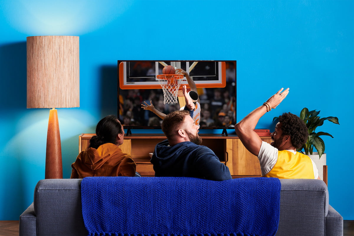 Three men watch a basketball game on TV