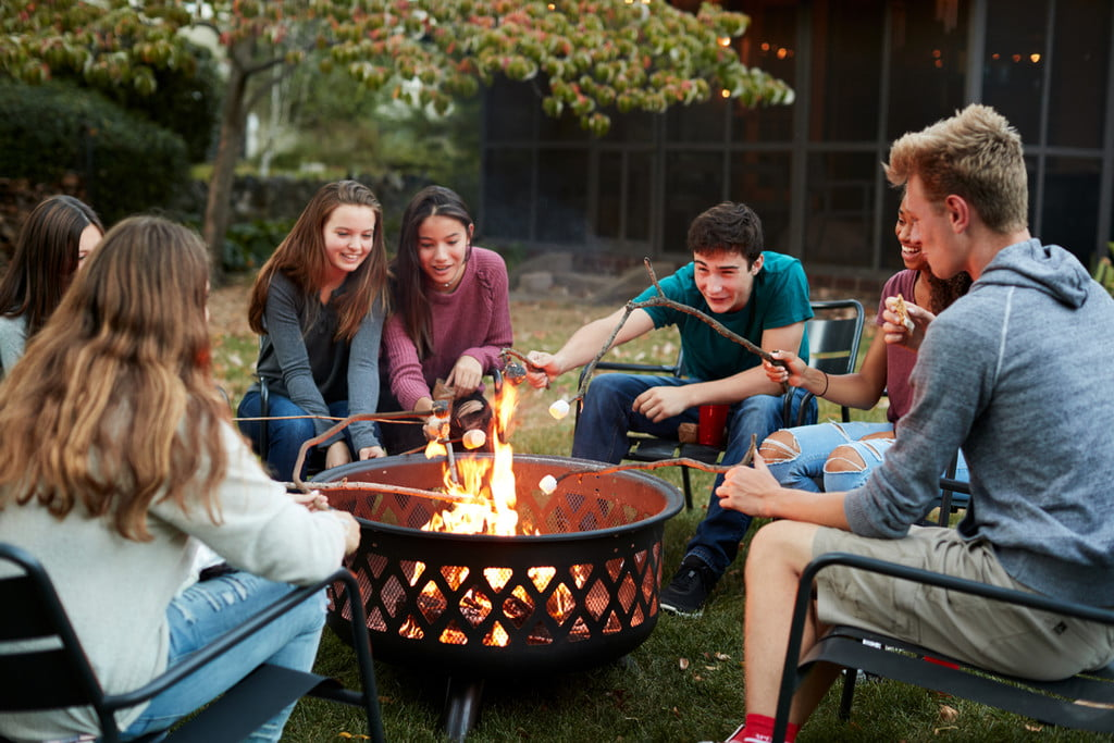 teenage friends toasting marshmallows around a fire pit