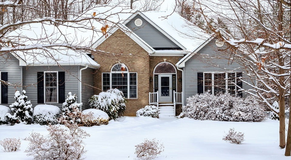 house with vinyl siding and brick in winter
