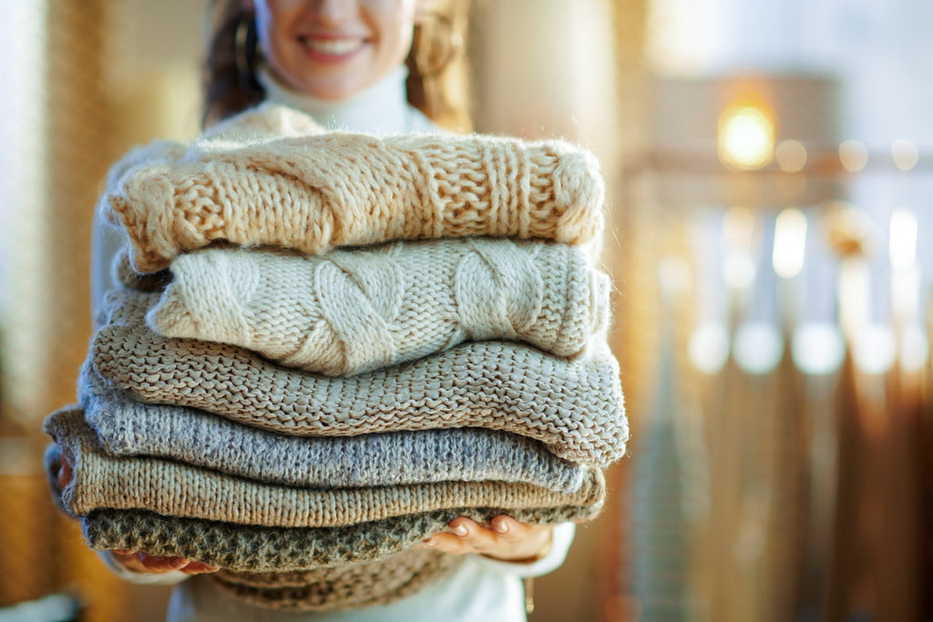 woman carrying folded winter sweaters