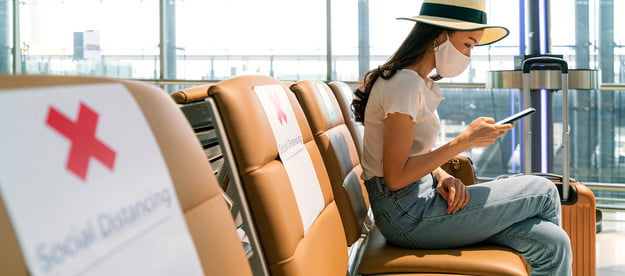 Woman wearing a mask sitting at the airport