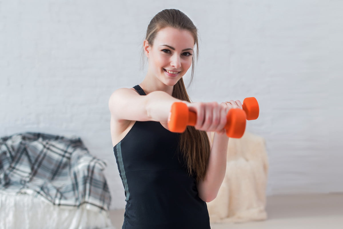 A woman uses boxing exercises to stay fit at home.