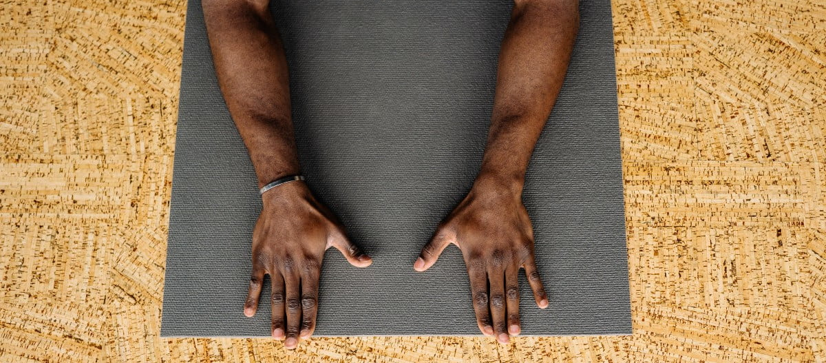 a man in child's pose on a black yoga mat