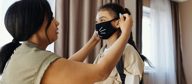A mom putting a mask on her child.
