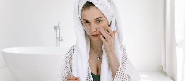A woman applying skincare products to her face.