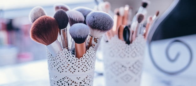 Two cups of makeup brushes sitting on a table.