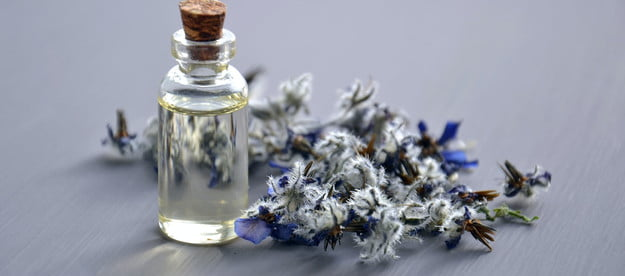 A bottle of fragrance and some flowers on a table.