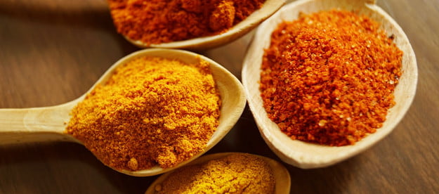Different spices, like turmeric, in spoons laying on a table.