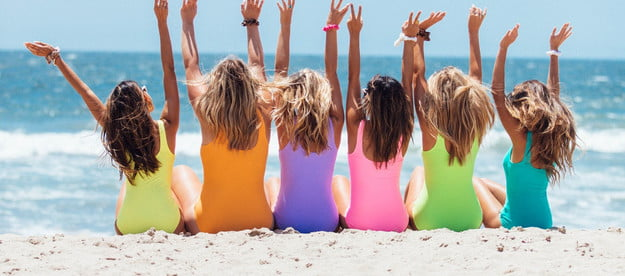 A group of females sitting on the beach facing the water so you see their backs and beachy hair.