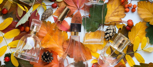 Perfumes laying on a bed of colorful fall leaves.