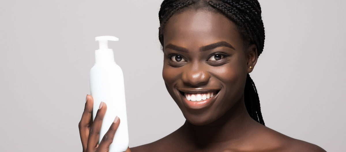 A woman holding a lotion bottle.