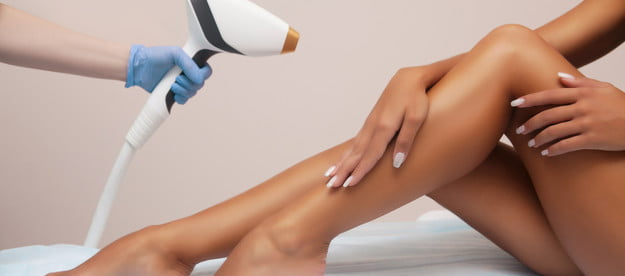 A woman getting hair removal done on her legs.