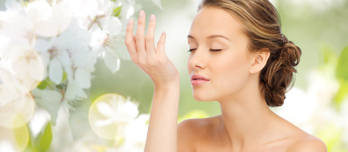 A woman smelling the scent on her wrist.