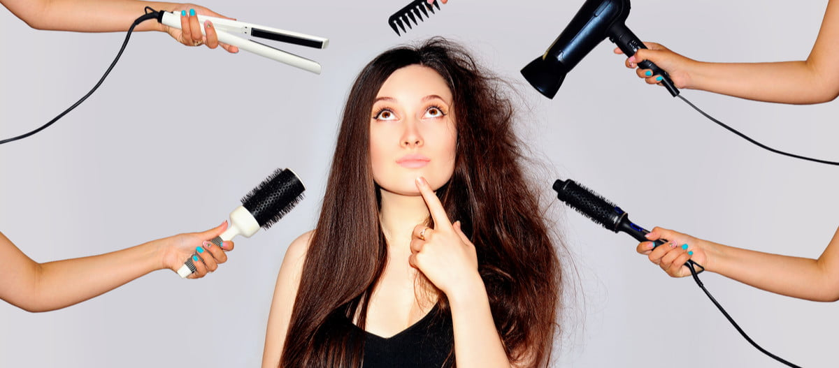 A woman looking at hair care tools that could be damaging her hair.