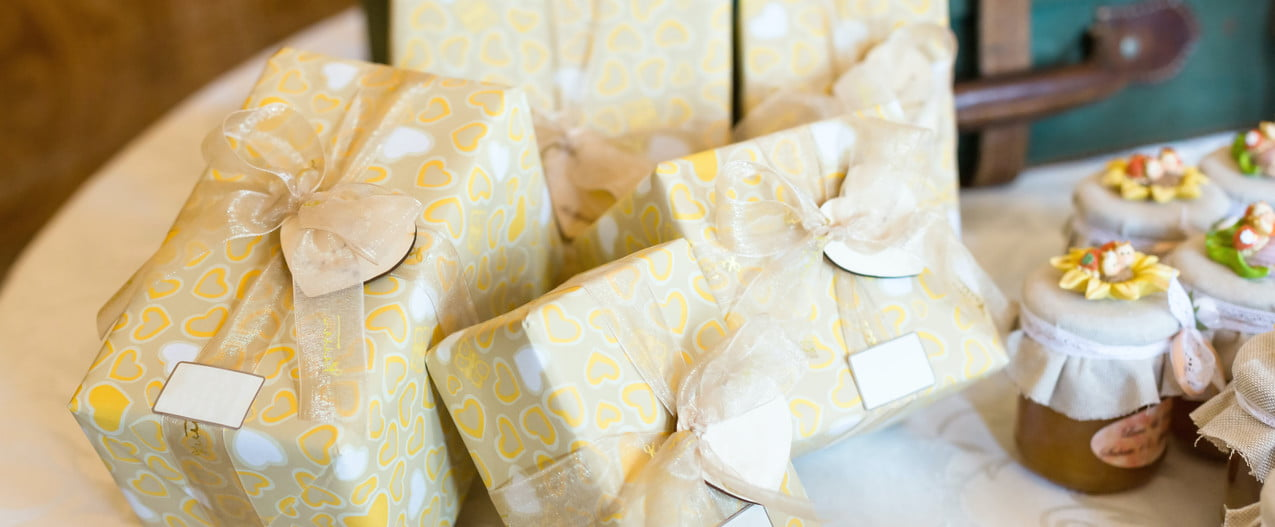 a pile of white and gold wedding gifts on a decorated table