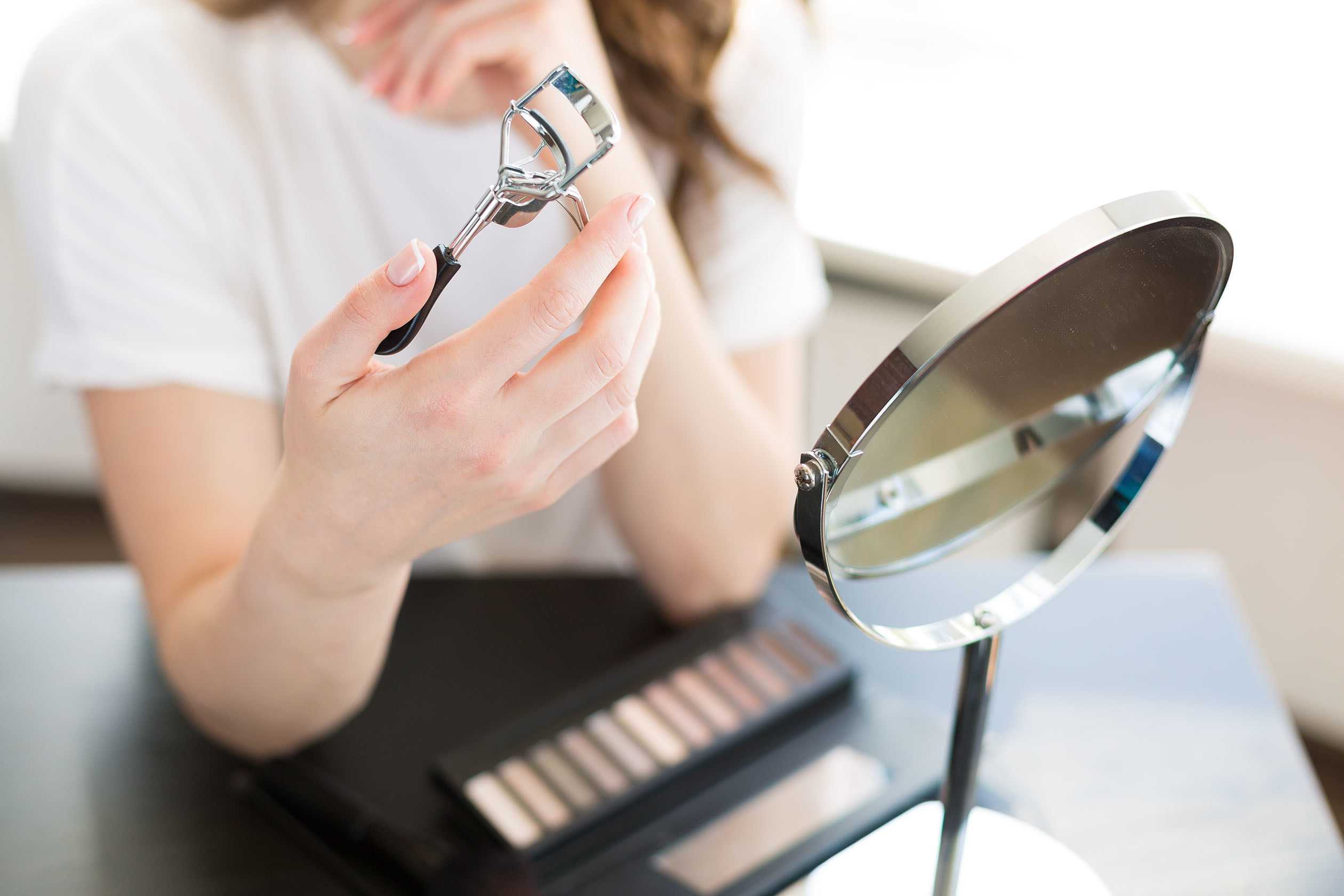 woman applying makeup and curling eyelashes in a mirror