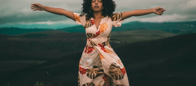 woman in a dress with arms outstretched outside