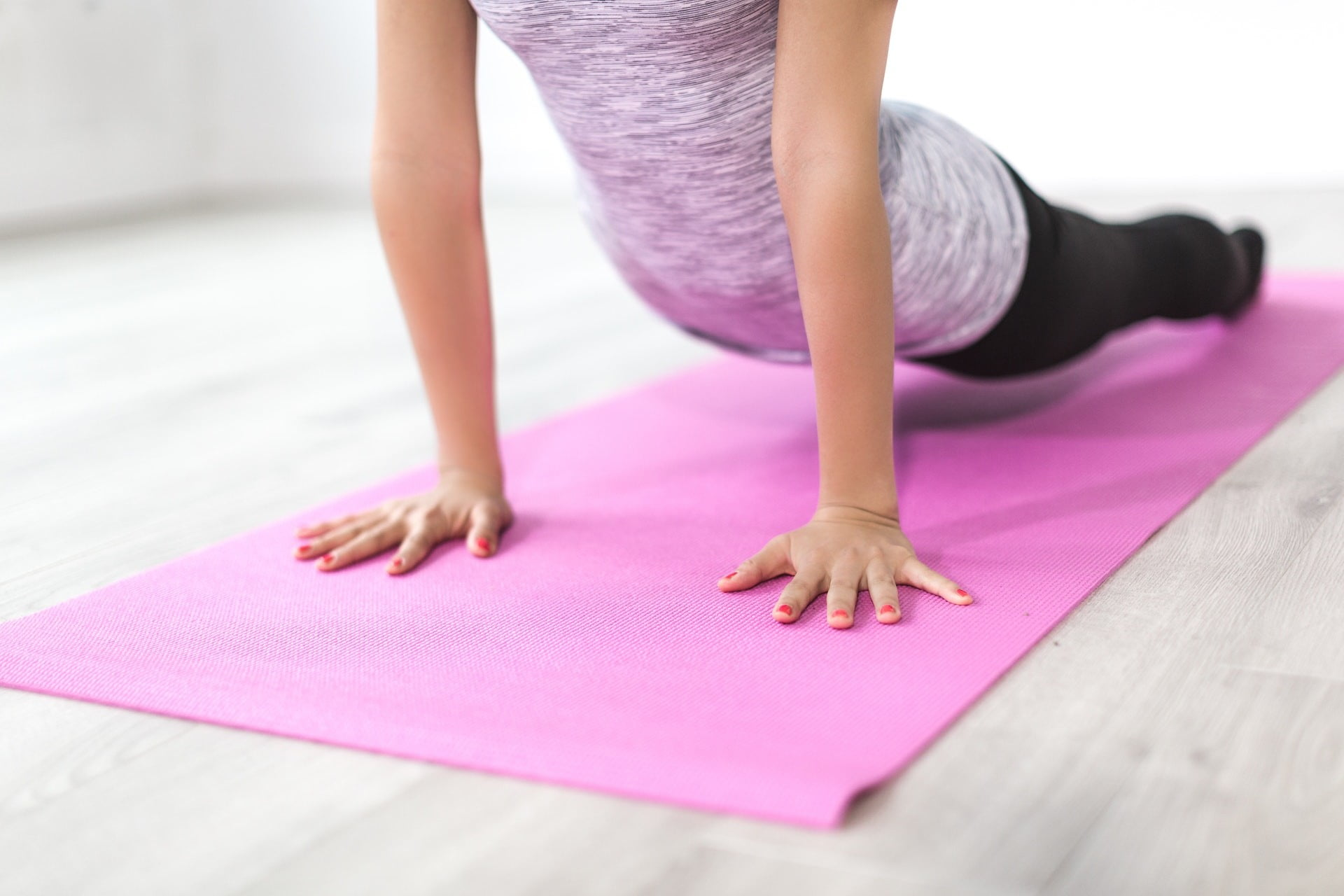 A woman doing yoga on a purple mat.