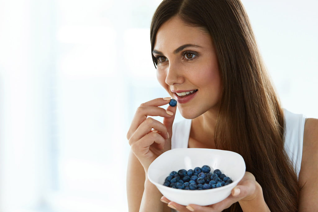 A woman eats blueberries to boost memory