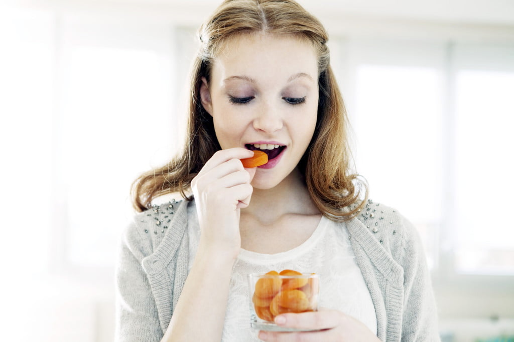 A woman eating dried apricots