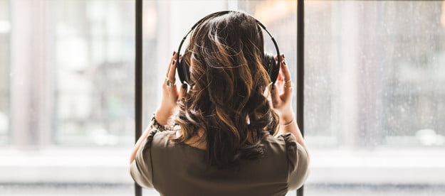 woman-relaxing-listening-to-podcast-by-window