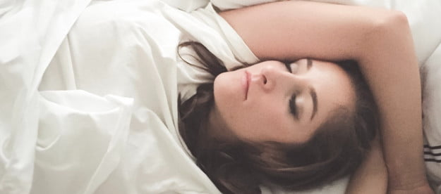 woman-sleeping-in-bed-white-sheets