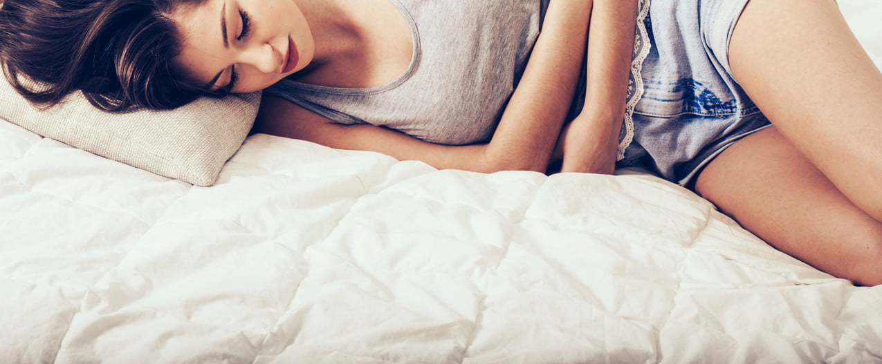Woman lying in bed holding abdomen