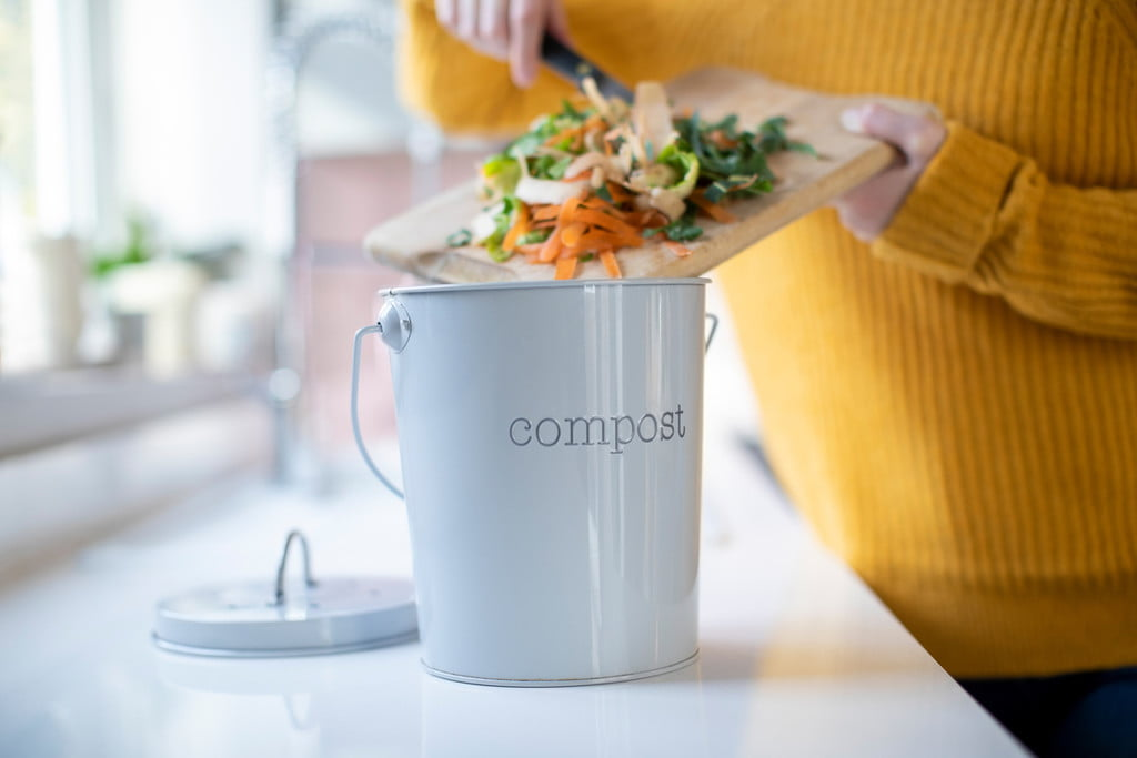A small bucket labeled compost on a counter. A woman puts scraps into it.