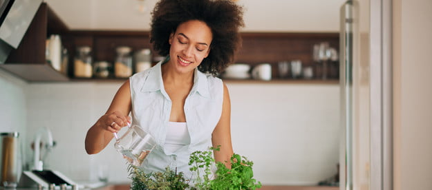woman watering herb plants on a kitchen counter