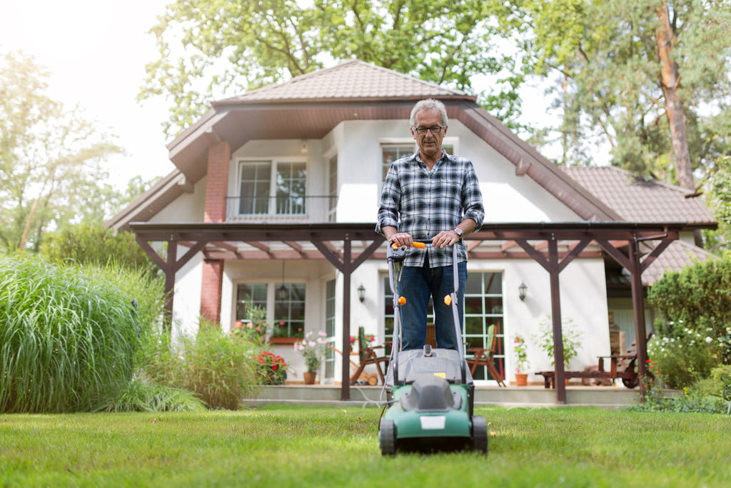 Man in blue and white shirt mowing his lawn with a small green push mower.