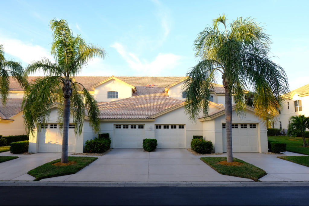 home garage and driveway with palm trees on either side