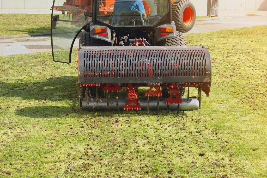 ride on core aerator working on a lawn