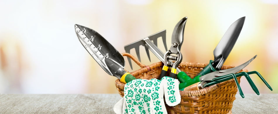 A small wicker basket on a table containing several gardening tools with green and yellow handles and floral gardening gloves