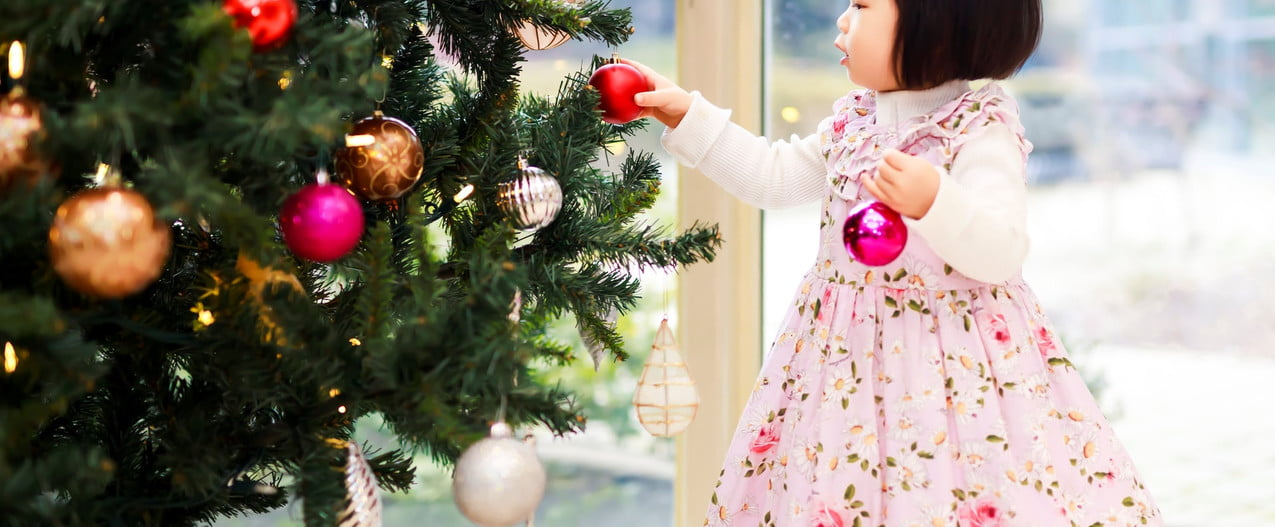 a little girl putting decorations on a Christmas tree