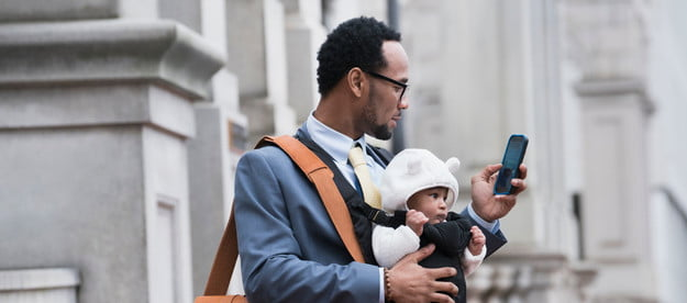 Man with baby, bag, and phone