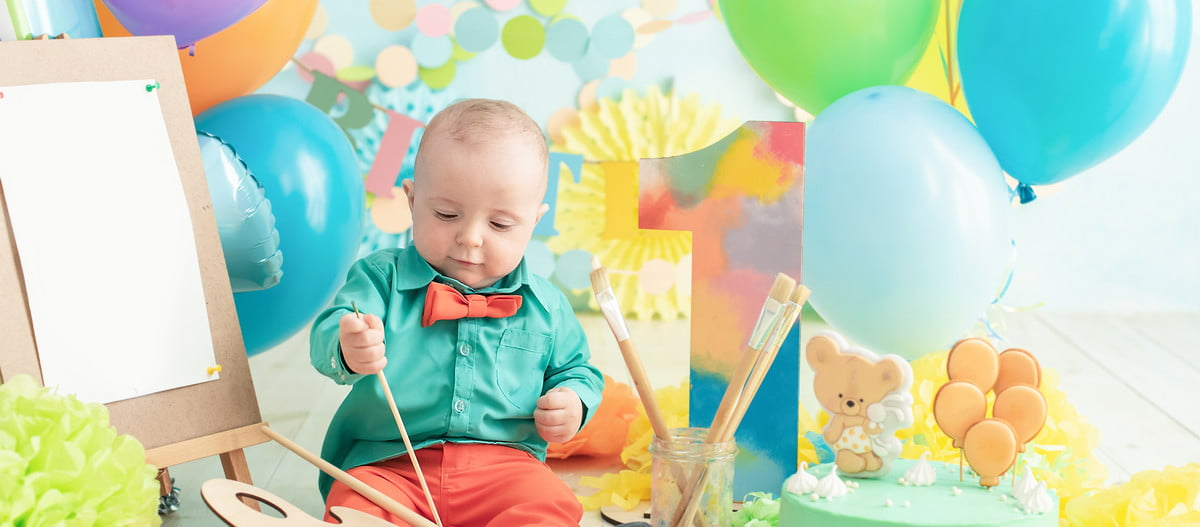Baby boy painting with balloons and cake for his first birthday
