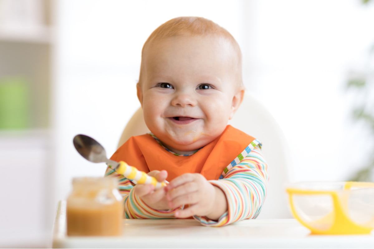 Smiling baby in a high chair with a spoon