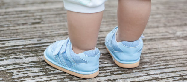 Child wearing baby shoes outside